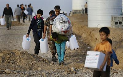Displaced Iraqi boys, who fled from Mosul with their families, carry food and other aid supplies, at a camp for internally displaced people in Hassan Sham, east of Mosul, Iraq, Saturday, Nov. 12, 2016.  (AP Photo/Hussein Malla)