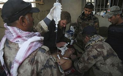 Iraqi special forces soldiers from the medical unit, and an American medic volunteer, center left, treat an injured man who was wounded by a mortar shell at a field hospital, in the Samah front line neighborhood, in Mosul, Iraq, Sunday, Nov. 27, 2016. (AP Photo/Hussein Malla)