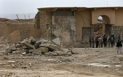 Iraqi soldiers and journalists gather at the damaged ancient site of Nimrud, which was destroyed by the Islamic State militants, southeast of Mosul, Iraq, November 16, 2016. (AP/Hussein Malla)