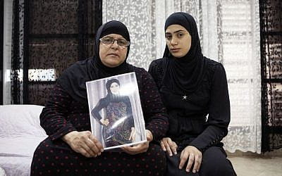 Israeli Arab Majeda Abu Sharkh left, holds a picture of her daughter Duaa Abu Sharkh who was killed in Lod after years of abuse and death threats. Her niece Alaa Khalili, sits with her, Thursday, November 3, 2016. (AP Photo/Dan Balilty)