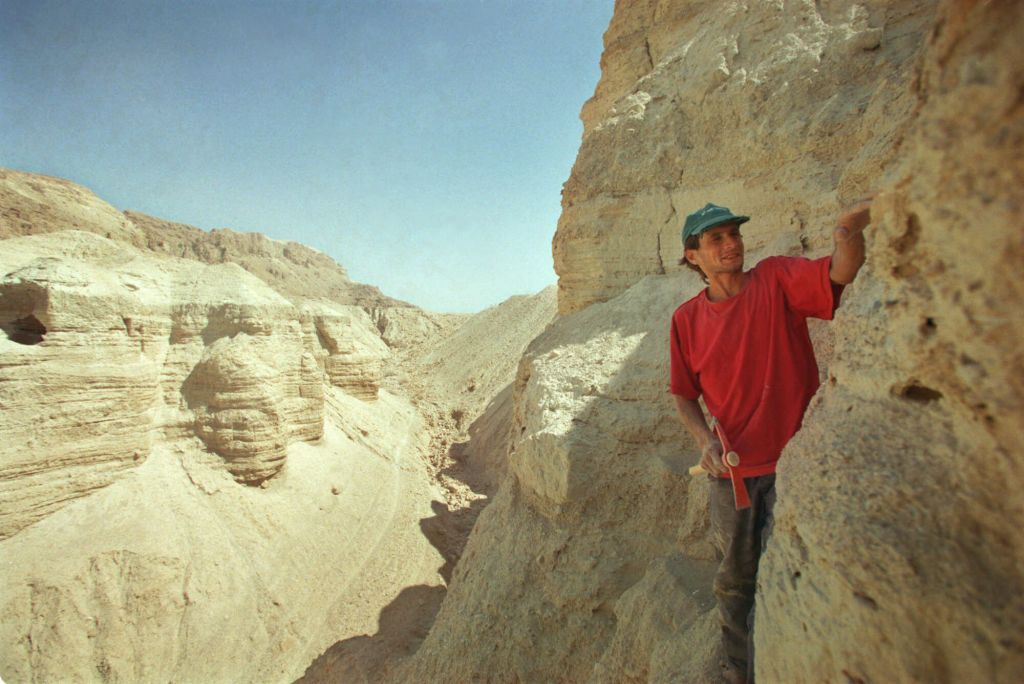 Roi Porat, an Israeli student of archaeology, works near the remains of a cave found at the West Bank archeological site of Qumran, near the Dead Sea Thursday, July 26, 2001. An Israeli antiquities official said November 14, 2016, that Israel is embarking on a major expedition to find more Dead Sea Scrolls and other artifacts. (AP Photo/Lefteris Pitarakis, File)