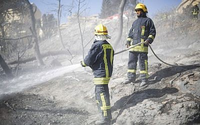 Palestinian firefighters work in Haifa, Israel, Friday, Nov. 25, 2016. Firefighters have reined in a blaze that spread across Israel's third-largest city of Haifa and forced tens of thousands of people to flee their homes. (AP Photo/Ariel Schalit)
