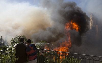 Men hose down wildfires in Haifa, Israel, November 24, 2016. (AP Photo/Ariel Schalit)