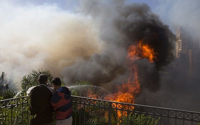 Men hose down wildfires in Haifa, Israel, November 24, 2016. (AP Photo/Ariel Schalit)