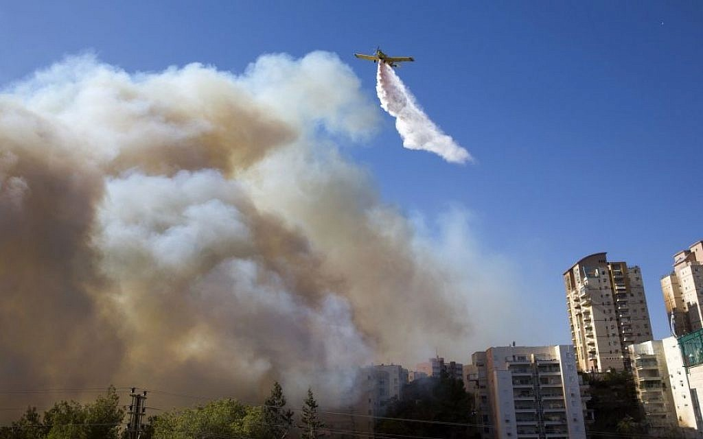 A plane drops firefighting material to extinguish wildfires in Haifa on November 24, 2016. (AP Photo/Ariel Schalit)