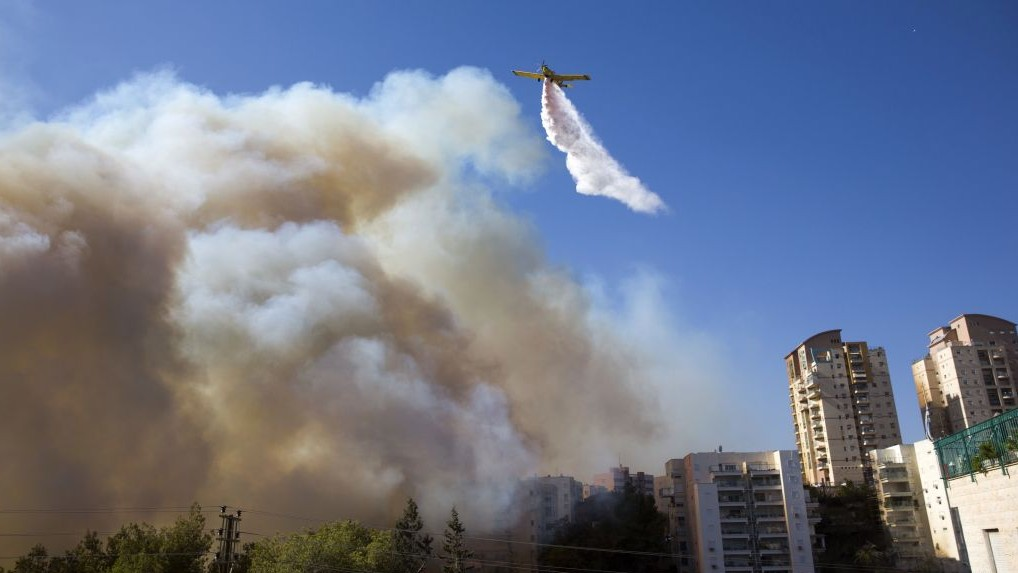 A plane flies tries to extinguish wildfires in Haifa, Israel, Thursday, November 24, 2016. (AP Photo/Ariel Schalit)