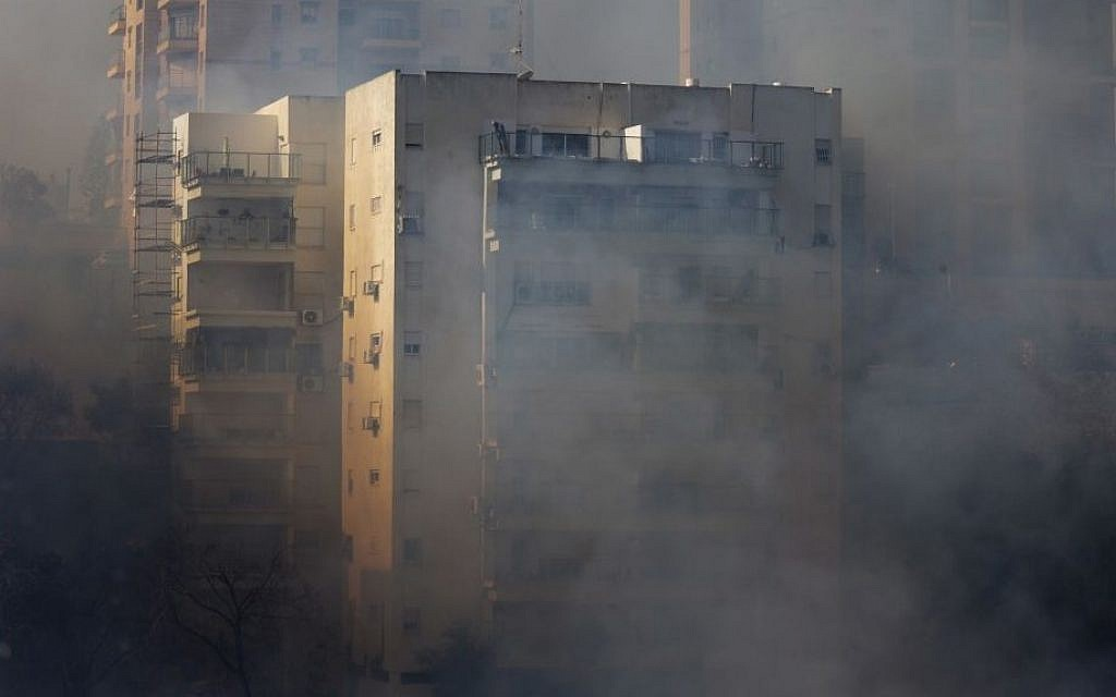 A man on the top floor of an apartment building looks at wildfires in Haifa, Israel, Thursday, November 24, 2016.  (AP Photo/Ariel Schalit)