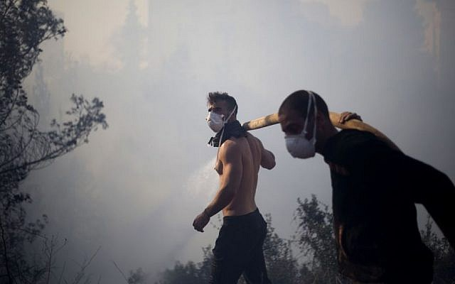 Residents fight a wildfire in Haifa, Israel, Thursday, Nov. 24, 2016. The blaze ripped through parts of Israel's third-largest city, forcing tens of thousands of people to evacuate their homes (AP Photo/Ariel Schalit)