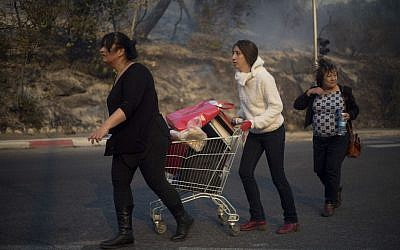 People carry their belongings inside a supermarket cart as they evacuate from wildfires in Haifa, Israel, Thursday, Nov. 24, 2016.  (AP Photo/Ariel Schalit)
