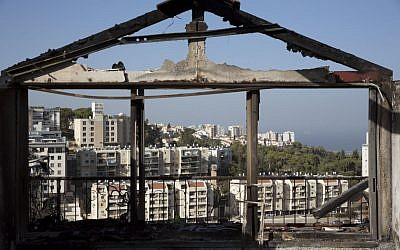 The Mediterranean sea and parts of the city can bee sen through a burned house following wildfires in Haifa, Israel, Friday, Nov. 25, 2016. (AP Photo/Ariel Schalit)