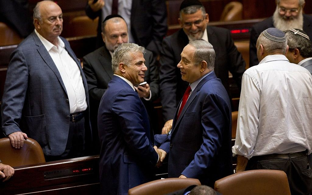 Prime Minister Benjamin Netanyahu (right) shakes hands with Yair Lapid, leader of the Yesh Atid party, in the Knesset plenum, October 31, 2016. (AP Photo/Sebastian Scheiner)