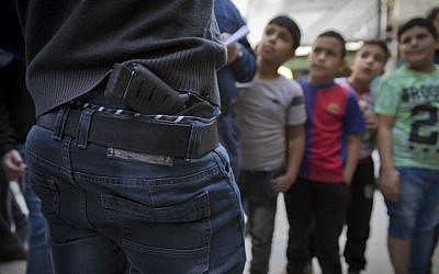 In this photo taken Thursday, Novemver 10, 2016, Palestinian refugee boys gather by armed men who are wanted by the Palestinian Authority security, one with a concealed weapon, in Balata refugee camp, in the West Bank. (AP Photo/Nasser Nasser)
