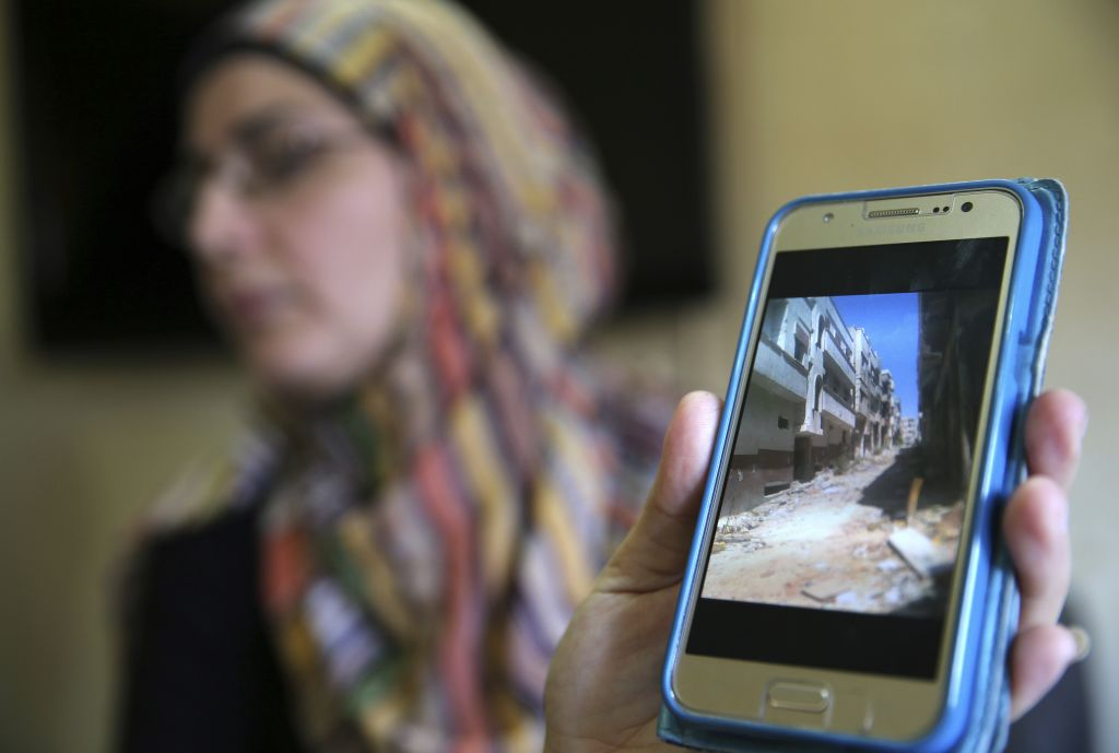 In this picture taken on Friday, Oct. 3, 2016, Hoda a Syrian displaced woman shows through her mobile phone the empty street of her house at Baba Tadmor neighborhood in Homs province, as she speaks during an interview with the Associated Press, in Tripoli, north Lebanon. (AP Photo/Hussein Malla)