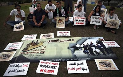In this picture taken on Friday, Oct. 7, 2016, Syrian citizens attend a sit-in against the forced displacement in Syria, in front the United Nations headquarters, in downtown Beirut, Lebanon. (AP Photo/Hussein Malla)
