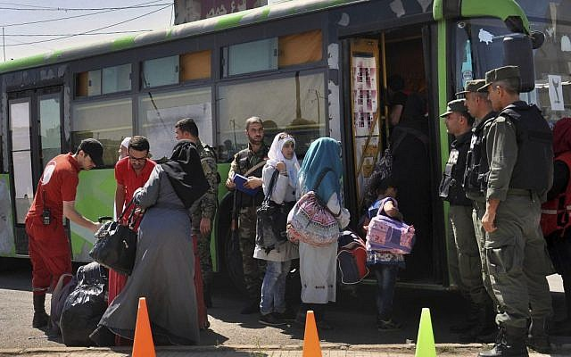 In this Monday, September 26, 2016, file photo, families of anti-Syrian government fighters, head to a bus as they leave the last besieged rebel-held neighborhood of Al-Waer in Homs province, Syria.  (SANA via AP, File)