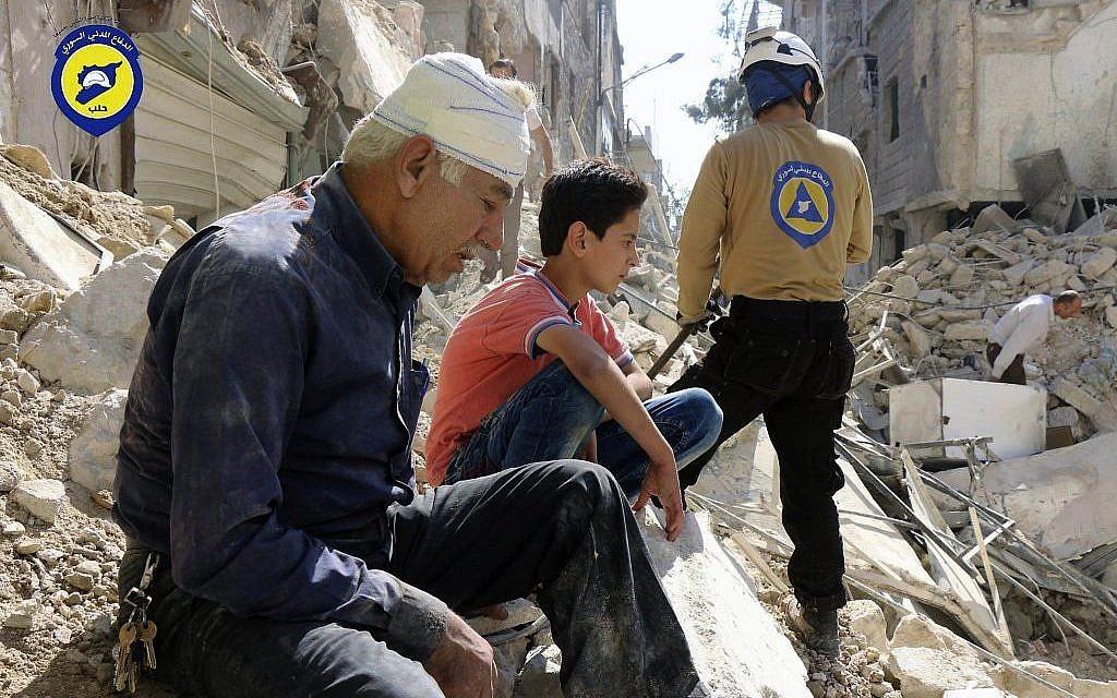Residents sit among rubble in rebel-held eastern Aleppo, Syria, October 11, 2016. (Syrian Civil Defense- White Helmets via AP, File)