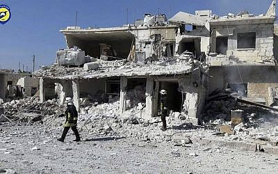 This photo provided by the Syrian Civil Defense White Helmets shows Civil Defense workers walk past damaged buildings after airstrikes hit in Abian Saman town, in rural western Aleppo province, Syria, Saturday, Nov. 5, 2016. (Syrian Civil Defense White Helmets via AP)