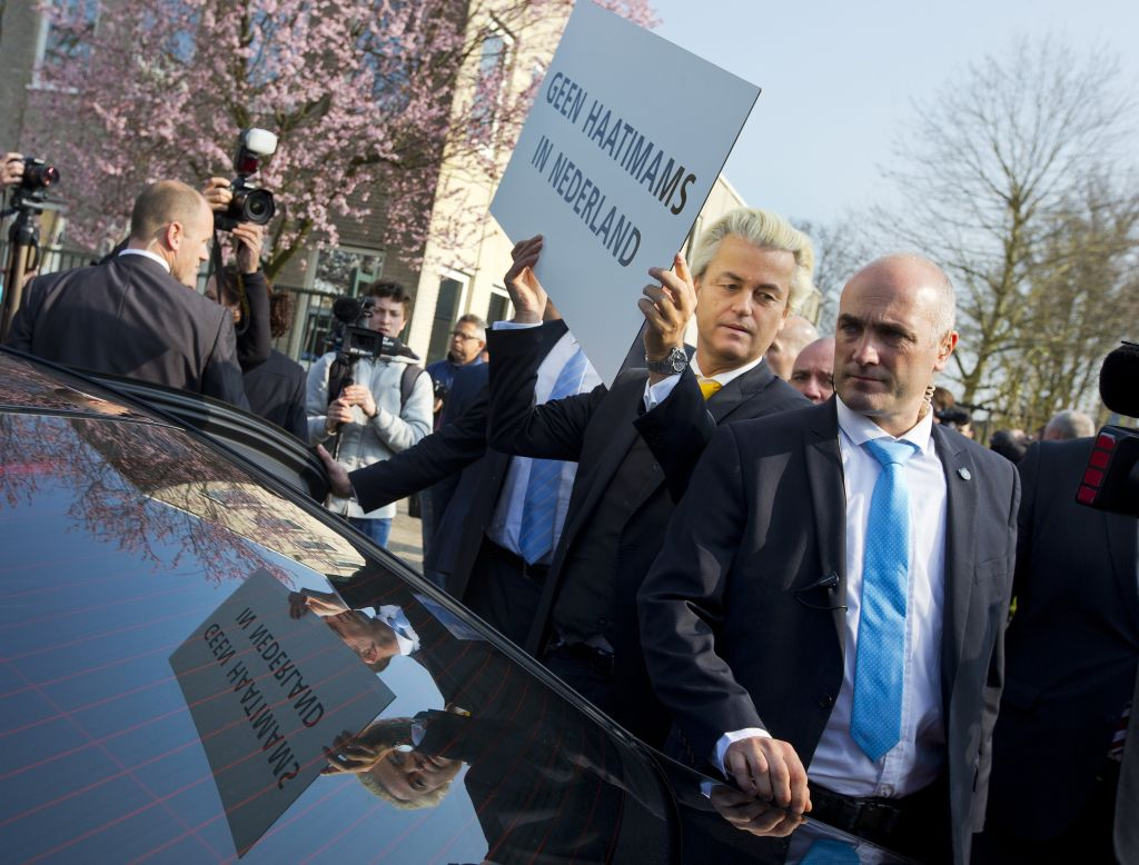 "Geert Wilders, leader of the anti-Islam Freedom Party, holds a sign reading ""No Hate Imams in the Netherlands"" in Utrecht, central Netherlands, April 9, 2015. (AP Photo/Peter Dejong, File)"
