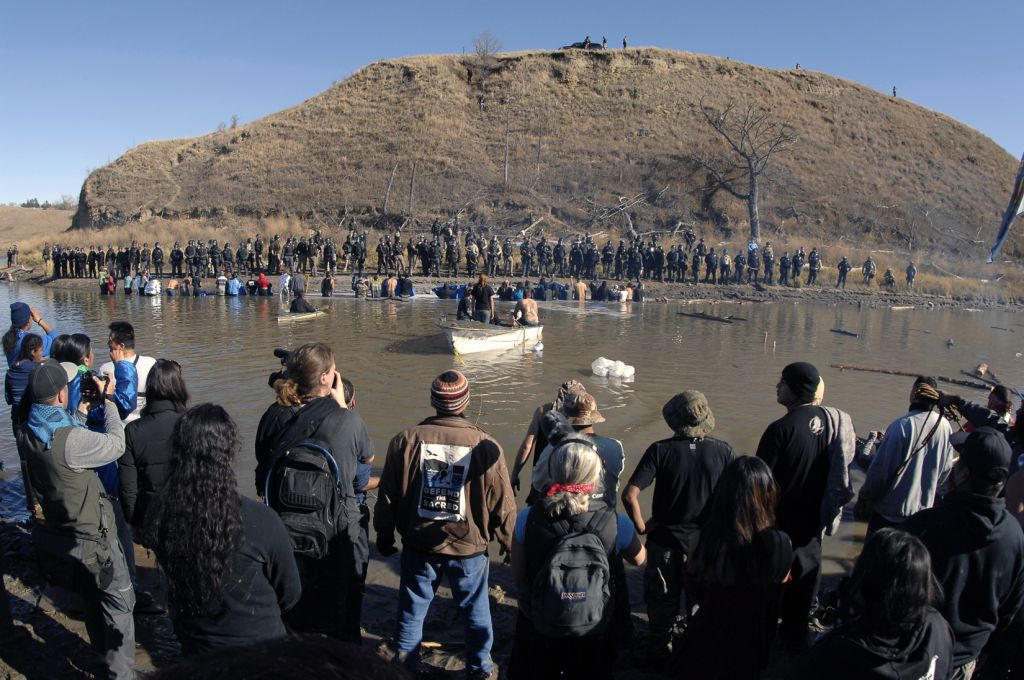 Dakota Access Pipeline protesters stand in the foreground and in the waist-deep water of the Cantapeta Creek, northeast of the Oceti Sakowin Camp, near Cannon Ball, North Dakota, Wednesday, November 2, 2016. (Mike Mccleary/The Bismarck Tribune via AP)