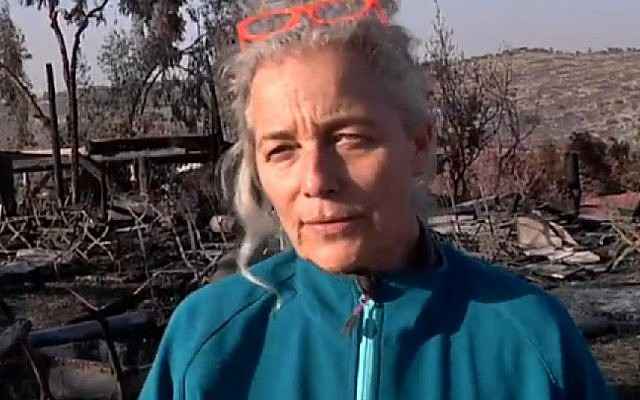 Rama Ben Zvi walking amid the smoldering embers of her burned down restaurant, on Saturday, November 26 2016. (Screen capture Channel 2)