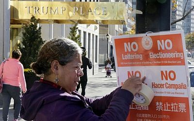 In this Nov. 8, 2016 file photo, poll interpreter Mayra Mora affixes a sign outside of a polling place in an apartment building named for then Republican presidential candidate Donald Trump, in New York. (AP/Richard Drew)