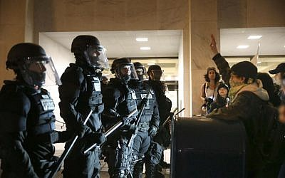Police stand in front of people who marched through downtown Portland, Ore., to protest of the election of president-elect, Donald Trump, Friday, Nov. 11, 2016. (Stephanie Yao Long/The Oregonian via AP)