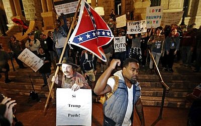 A Trump supporter with a flag, left, counter protests as a small group outside the courthouse protests in opposition of President-elect Donald Trump, Friday, November 11, 2016, in Fort Worth, Texas. (Brandon Wade/Star-Telegram via AP)