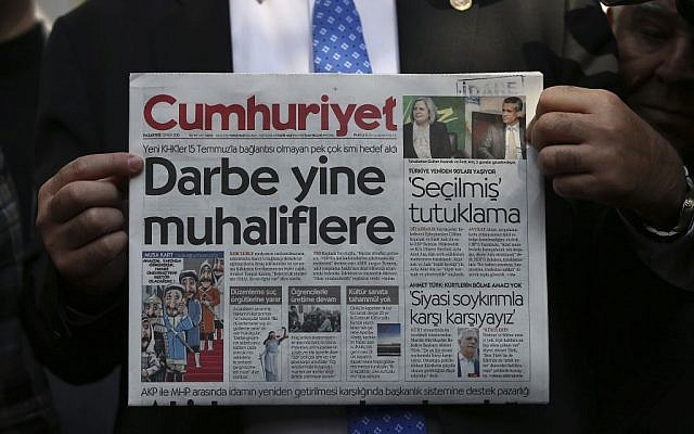 A man holds the latest copy of the Cumhuriyet newspaper outside its Istanbul headquarters after police detained chief editor Murat Sabuncu and two columnists of the opposition newspaper, October 31, 2016. (AP Photo/Emrah Gurel)