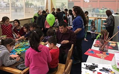 Member's of Berlin's Jewish community volunteer with refugee children at the Spandau refugee center, with arts and crafts in front and face painting in back. November 13, 2016. (Courtesy)