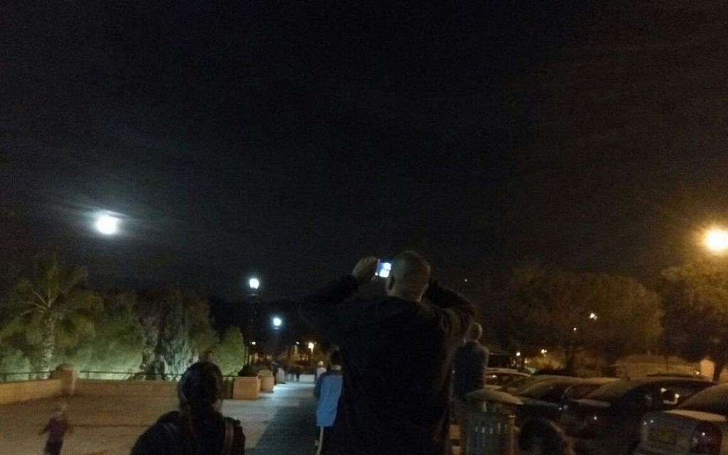 An Israeli man takes a picture of the 'supermoon' on Jerusalem's promenade on November 14, 2016. (Joshua Davidovich/Times of Israel)