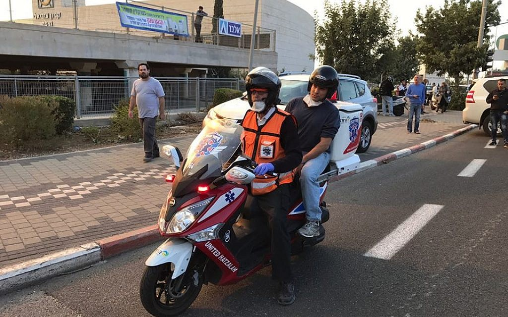Education Minister Naftali Bennett rides pillion on a United Hatzalah ambucycle to assess the situation in Haifa on November 24, 2016, as fires rage across the city. (United Hatzalah)