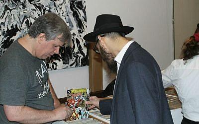 A man examining a comic book for sale at the inaugural Jewish Comic Con, held at Congregation Kol Israel, a Brooklyn synagogue, November 13, 2016. (Ben Sales/JTA)