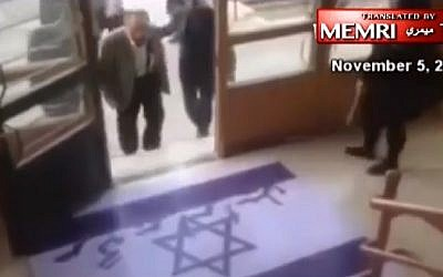 An Iranian professor avoids stepping on an Israeli flag painted onto the ground at a university in northeastern Iran, in footage released November 5, 2016. (MEMRI/screenshot)