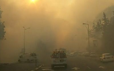An ambulance makes its way through the smoke-filled streets of Haifa as firefighters battle to control a massive blaze across the city on November 24, 2016 (screen capture: Channel 10)