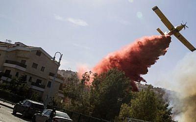 An Israeli firefighter plane helps extinguish a bushfire in the northern Israeli port city of Haifa on November 24, 2016. AFP PHOTO / JACK GUEZ