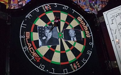 An image of Hillary Clinton is speared by a dart on a dartboard at Mike's Place bar in Jerusalem early November 9, 2016. Donald Trump supporters were watching the results of the US presidential race at the watering hole. (Melanie Lidman/Times of Israel)