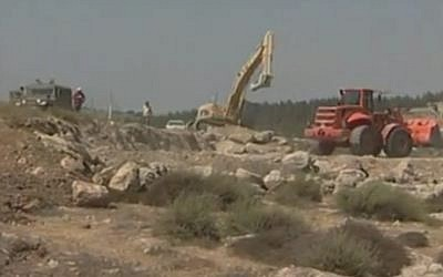 A bulldozer levels land for a construction project in the West Bank, as Israeli soldiers look on. (YouTube screenshot)