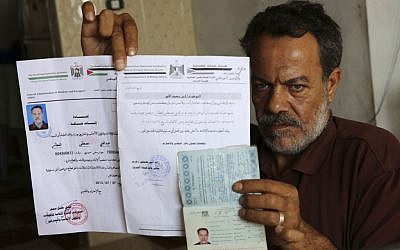 Syrian refugee, Majed al-Attar, poses while showing his expired Syrian passport and Palestinian identification documents at his family's rented house in Rafah, Gaza, October 31, 2016 (AP Photo/Adel Hana)