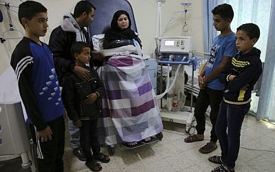 In this November 1, 2016 photo, Syrian refugee Kholoud Foura, who has developed muscular dystrophy, poses with her husband and their children, while tied to the bed and hooked up to a respirator, at Al-Wafa hospital, in Al Zahra City, central Gaza Strip. The family have slept in beds and mattresses in her hospital room for about a year and a half. (AP Photo/Adel Hana)