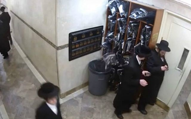 Screen capture of security camera footage showing a tefillin set falling from a cubby into a garbage bin at a Satmar Hasidic synagogue in Brooklyn, New York. (YouTube screen capture/Yeshiva World News)