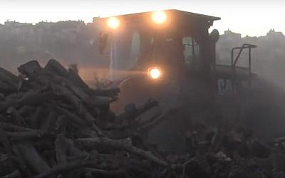 A Civil Administration tractor confiscates piles of wood from a West Bank charcoal plant, November 17, 2016. (COGAT spokesperson's office)