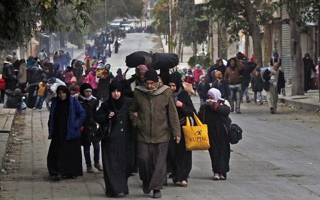 Syrian residents of eastern rebel-held parts of Aleppo walk through the Kadi Askar district as they leave their homes for a safer place in a distinct rebel-controlled area on November 30, 2016, during a Syrian army offensive on the eastern sectors of the divided city. (AFP PHOTO / THAER MOHAMMED)