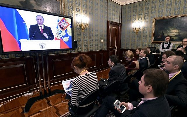 Journalists watch a live broadcast of Russian President Vladimir Putin's Federal Assembly address at a press room at the Kremlin in Moscow on December 1, 2016. (AFP /Natalia KOLESNIKOVA)