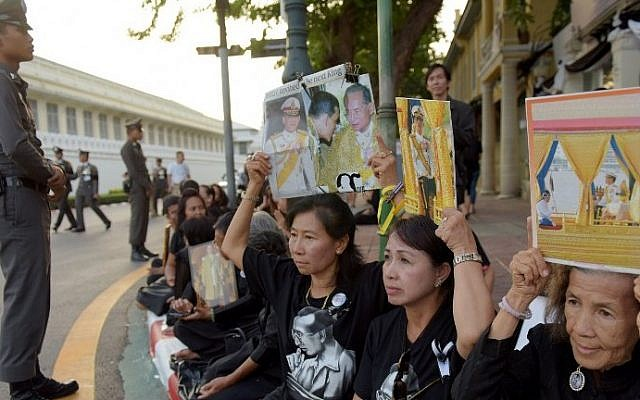 Women hold images of Thai Crown Prince Maha Vajiralongkorn with his father, the late Thai King Bhumibol Adulyadej, outside the Grand Palace in Bangkok on December 1, 2016. (AFP PHOTO/TANG CHHIN SOTHY)
