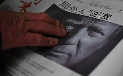 This file photo taken on November 10, 2016 shows a man buying a newspaper featuring a photo of US President-elect Donald Trump, the day after the US election, at a news stand in Beijing on November 10, 2016. The headline reads 'Outsider strikes back.' (AFP/Greg Baker)