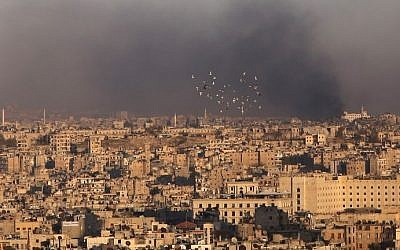 A general view taken from the government-held side of Aleppo shows smoke billowing during fighting between Syrian regime forces and rebel fighters in east Aleppo, on December 3, 2016. (AFP PHOTO / Youssef KARWASHAN)