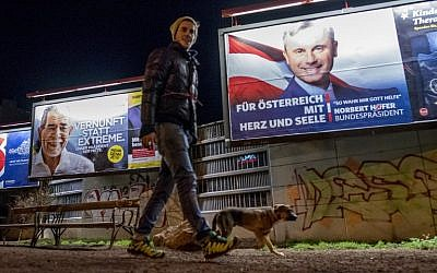 A man walks his dog around a park where Election posters of Austrian Presidential election candidates Norbert Hofer (R) of the Freedom Party Austria FPOe, and independent Alexander Van der Bellen (L) are seen in Vienna, Austria on December 3, 2016. (AFP PHOTO/JOE KLAMAR)