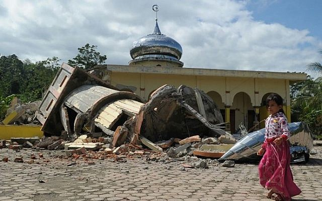Illustrative. An Acehnese girl walks past a collapsed mosque minater following an earthquake in Pidie, Aceh province, Indonesia,  on December 7, 2016. (AFP PHOTO/CHAIDEER MAHYUDDIN)