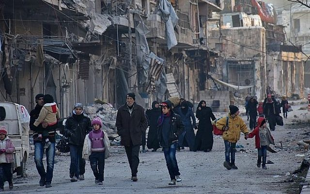 Syrian residents fleeing the violence in the eastern rebel-held parts of Aleppo evacuate from their neighbourhoods through the Bab al-Hadid district after it was seized by the government forces, on December 7, 2016. (AFP/GEORGE OURFALIAN)