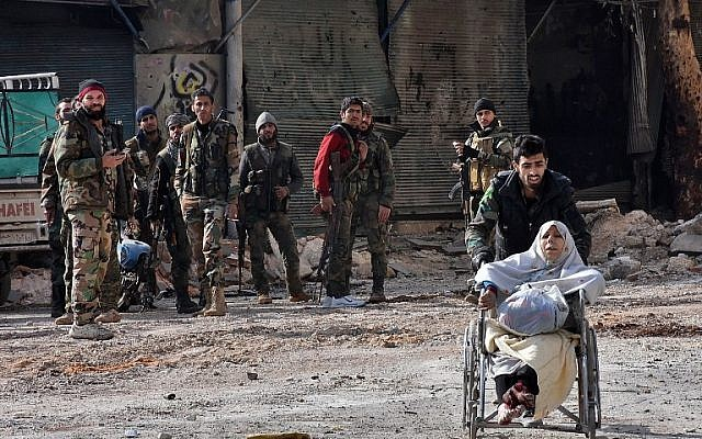 A regime soldier pushes an injured woman in a wheelchair as civilians are evacuated from Aleppo's al-Shaar neighborhood after government forces took control of the area in the eastern part of the northern Syrian city on December 7, 2016. (AFP PHOTO/GEORGE OURFALIAN)